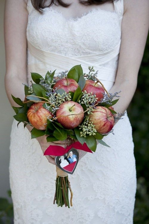 a fall wedding bouquet of apples, foliage and seeded eucalyptus plus a burgundy ribbon and a heart with photos