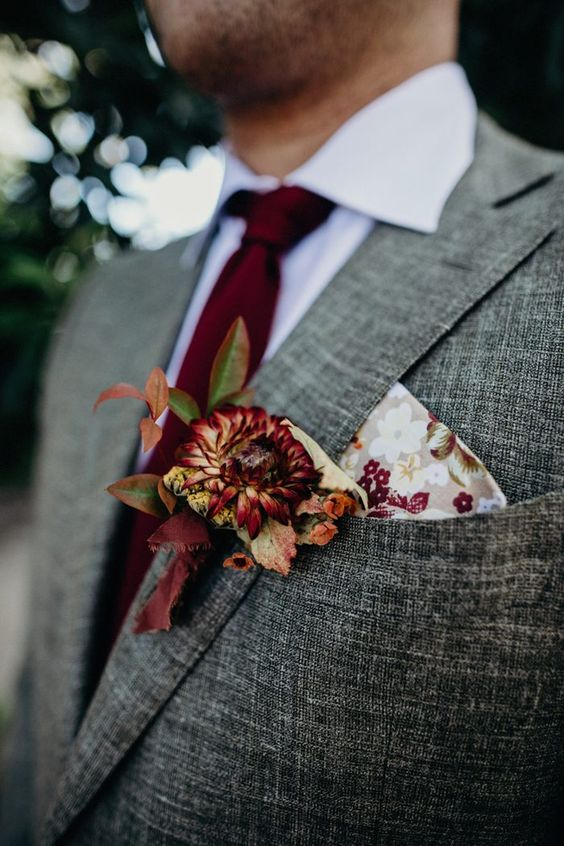 a fall wedding boutonniere with a burgundy bloom and bold leaves plus a floral pocket square is amazing
