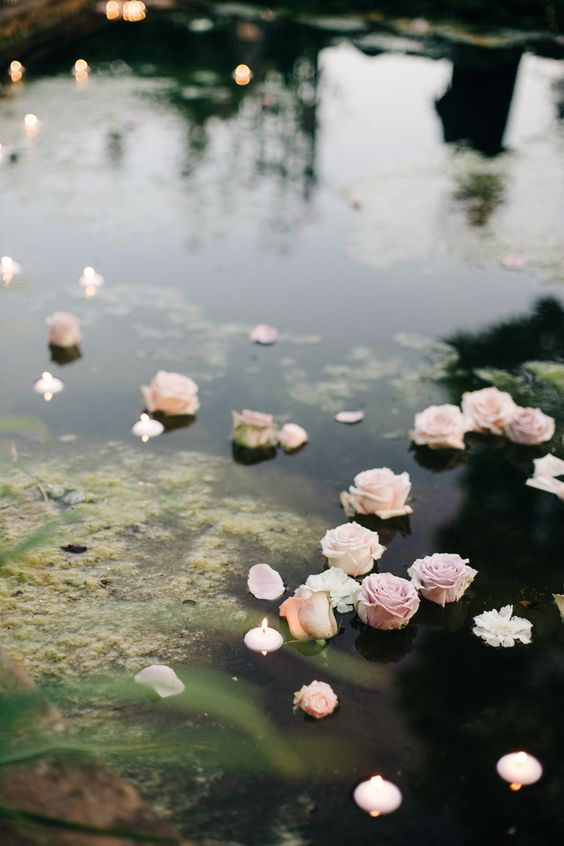a garden pond styled for the wedding with floating pink roses and candles is a very lovely idea to go for