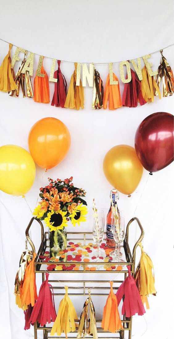 a glam and bright fall bridal shower bar with a colorful tassel garland with letters and a bright polka dot cart with blooms and balloons
