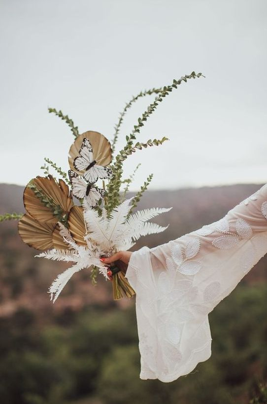 a gorgeous boho wedding bouquet of fronds, greenery, white dried greenery and butterflies is a lovely idea for a boho bride