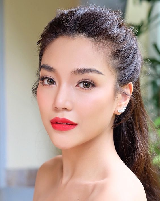 a gorgeous bold Asian makeup with a matte red lip, extended eyelashes, chic eyebrows and blushes looks amazing