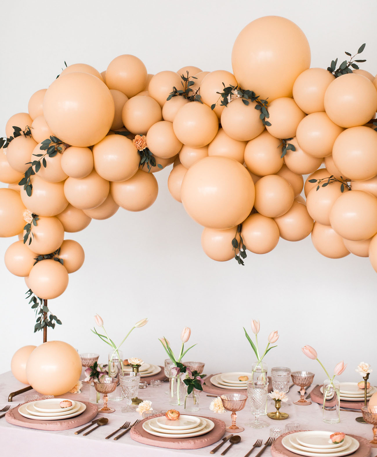 a gorgeous modern bridal shower setting in blush and peachy, with a balloon overhead decoration, blush tulips and textural chargers