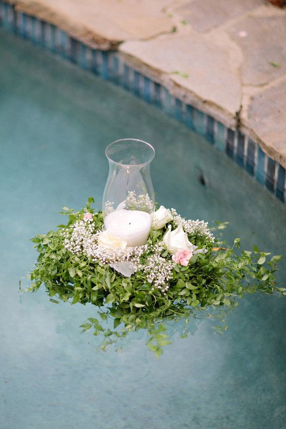 a greenery and pastel bloom arrangement with a single candle inside is a beautiful solution for wedding pool decor
