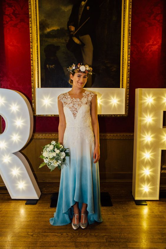 a high low A-line sleeveless wedding dress with a lace bodice and a dip dye skirt in blue and a train plus silver shoes