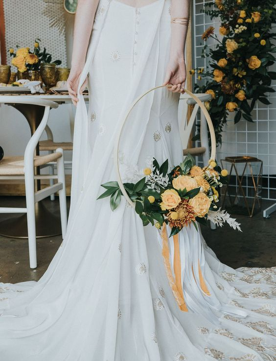 a hoop wedding bouquet with foliage and yellow blooms, with billy balls and some yellow ribbons is a very creative idea