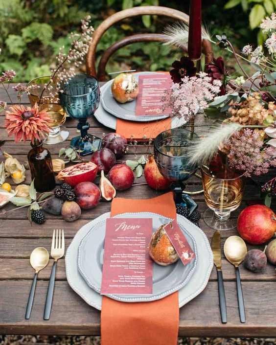 a jewel-toned tablescape with fresh fruits, bright blooms and feathers plus colored candles