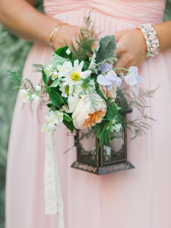 a lantern wedding bouquet covered with lush blooms and greenery is a fresh and non-traditional idea for a bride