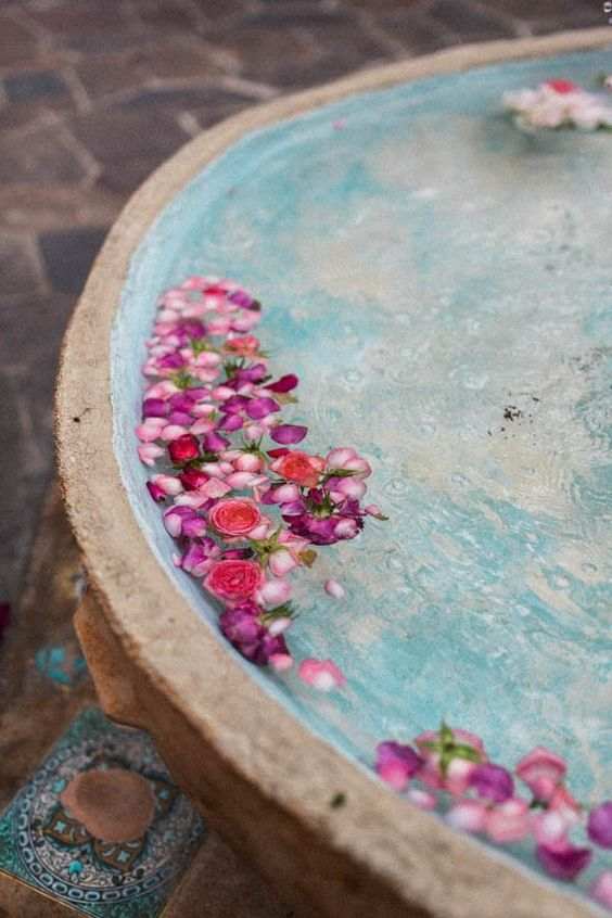 a large bowl with floating pink and hot pink blooms is a lovely idea for any wedding, especially an outdoor one