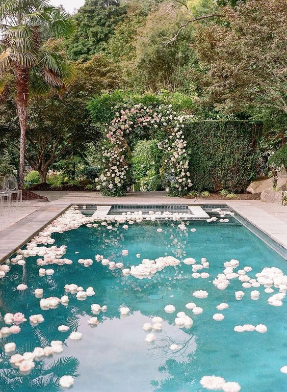 a large pool floating with white and blush blooms and a matching floral arch opposite it is a cool idea