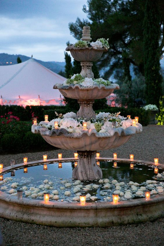 a large tiered fountain with white floating blooms and candles around it is a very cool and romantic idea to try