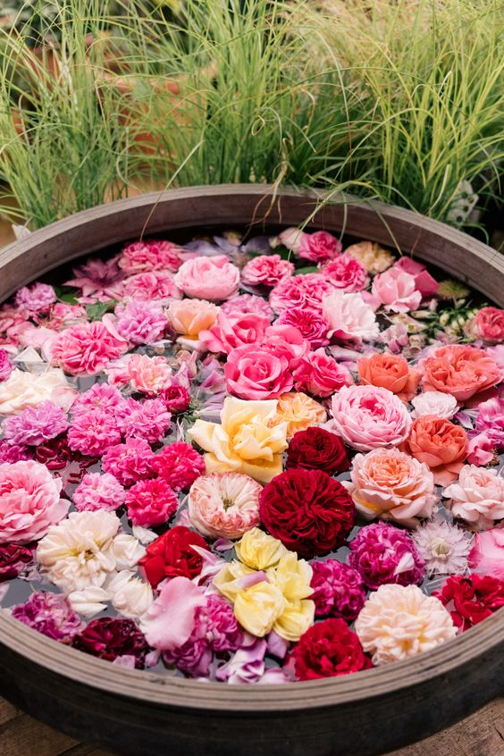 a large wooden bowls with lots of floating blooms in red, deep red, pink, hot pink and peachy shades is amazing