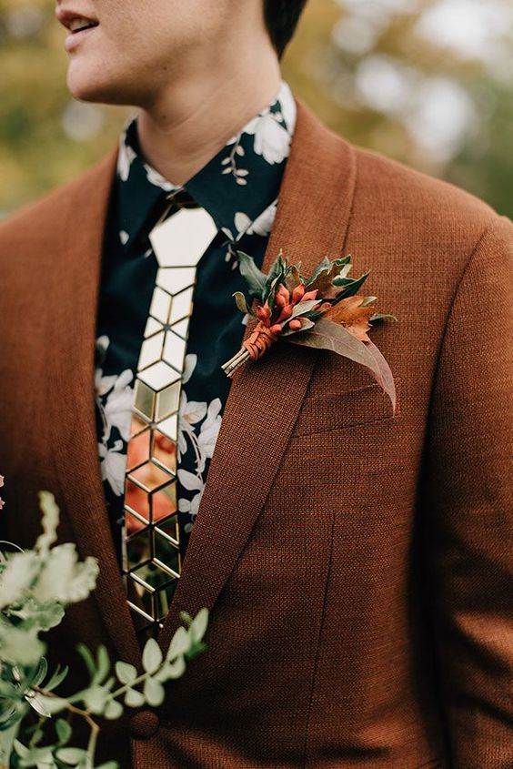 a lovely copper wedding boutonniere with green and rust leaves, berries and rust-colored wrap for a fall boho wedding