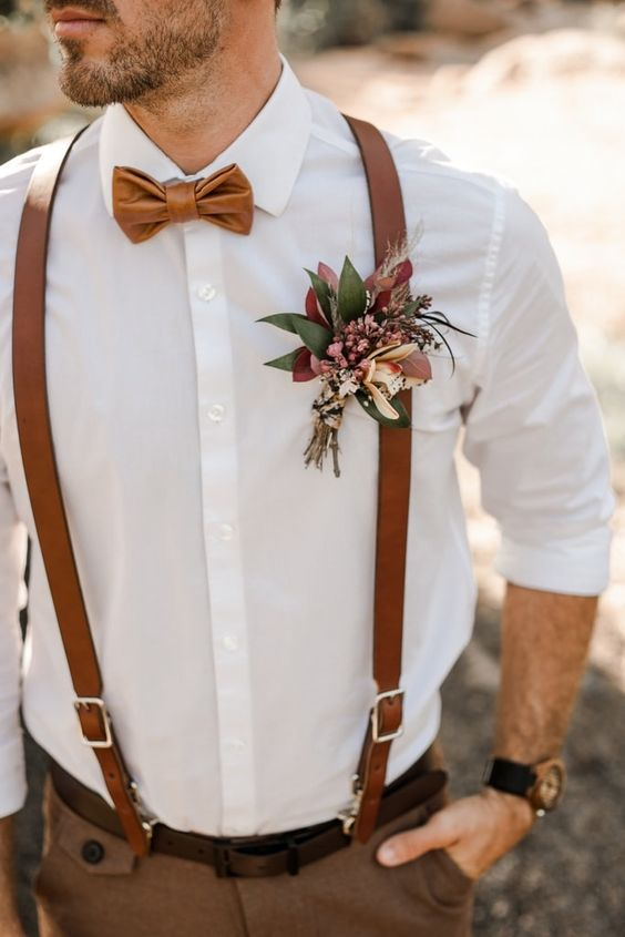 a lovely fall-colored wedding boutonniere with pink and peachy blooms, greenery and colorful leaves plus grasses