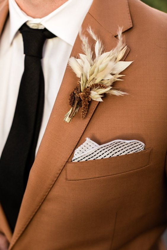 a lovely fall wedding boutonniere with rust colored blooms and white dried herbs and leaves is amazing for a fall boho wedding
