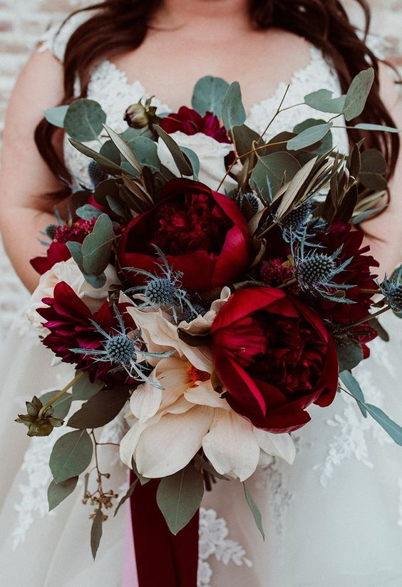a lush and bol fall wedding bouquet of oversized deep red peonies, greenery and thistles is just jaw dropping