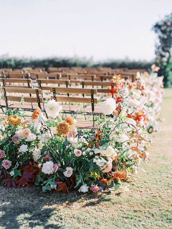 a lush fall wedding aisle with blush and dusty pink blooms, rust and orange ones and lots of greenery and bold foliage