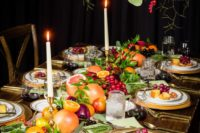 a lush harvest-inspired tablescape with lots of greenery and fresh fruits right on the table plus tall candles