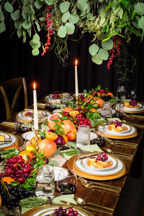 a lush harvest inspired tablescape with lots of greenery and fresh fruits right on the table plus tall candles