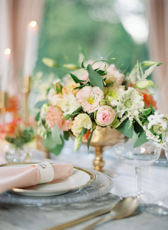 a luxurious wedding table setting with peachy, pink and rust blooms and greenery, pink napkins and gold candleholders and cutlery