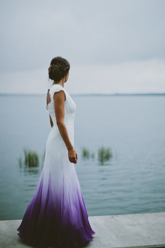 a mermaid white and purple dip dye wedding dress with a cutout back, cap sleeves and a draped bodice