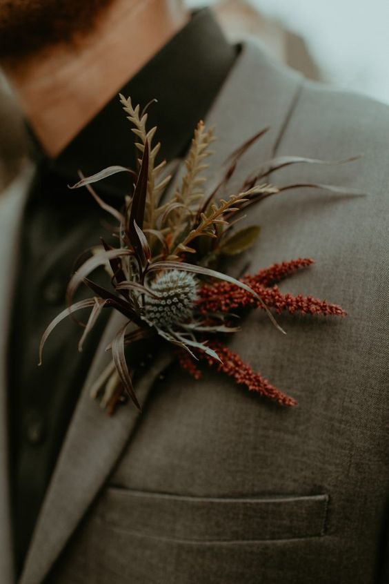 a moody wedding boutonniere with burgundy blooms, grasses and a thistle is a lovely idea for a fall wedding