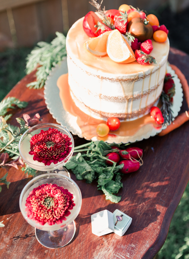 a naked wedding cake with caramel drip, fresh fruits and veggies on top and around,too