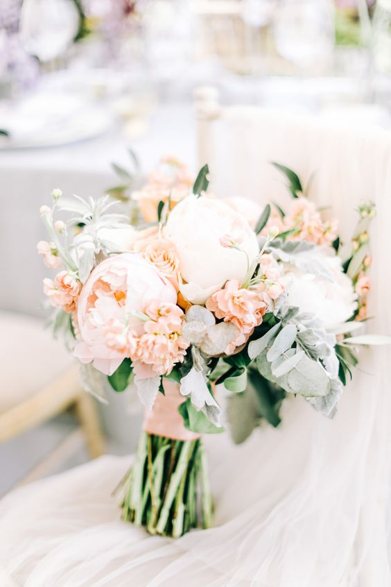 a pastel wedding bouquet with white and blush peonies, some greenery and a blush wrap is amazing for spring