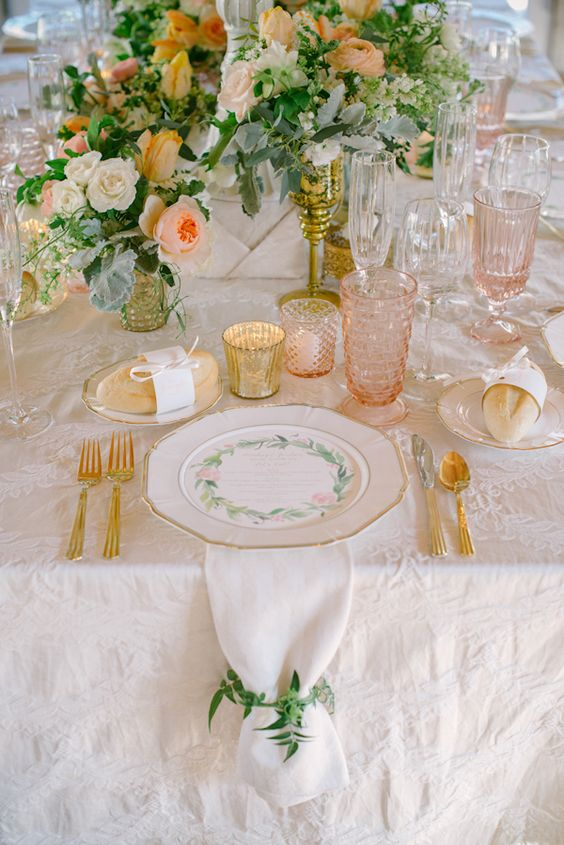 a peach and cream wedding table setting with peachy and white blooms and greenery, peachy glasses, gold cutlery and gold candleholders