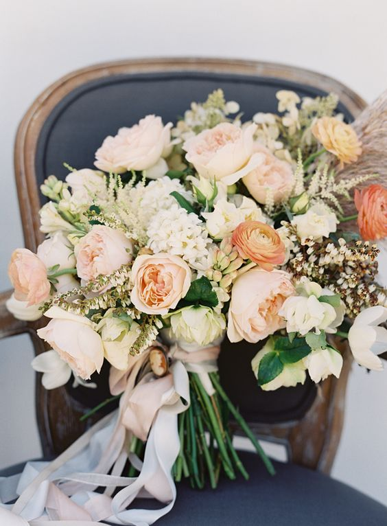 a peachy and creamy wedding bouquet with various blooms, greenery and even pampas grass plus white ribbons