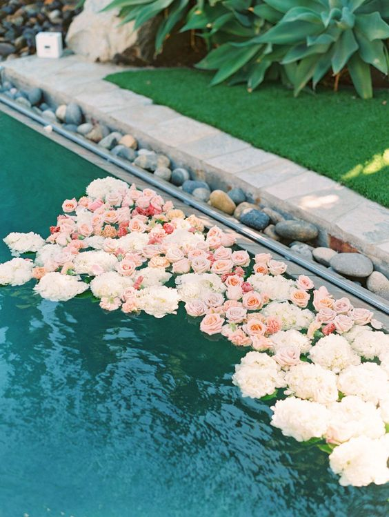 a pool lined up with pebbles and with floating neutral and pastel blooms is a refined and beautiful solution for a wedding