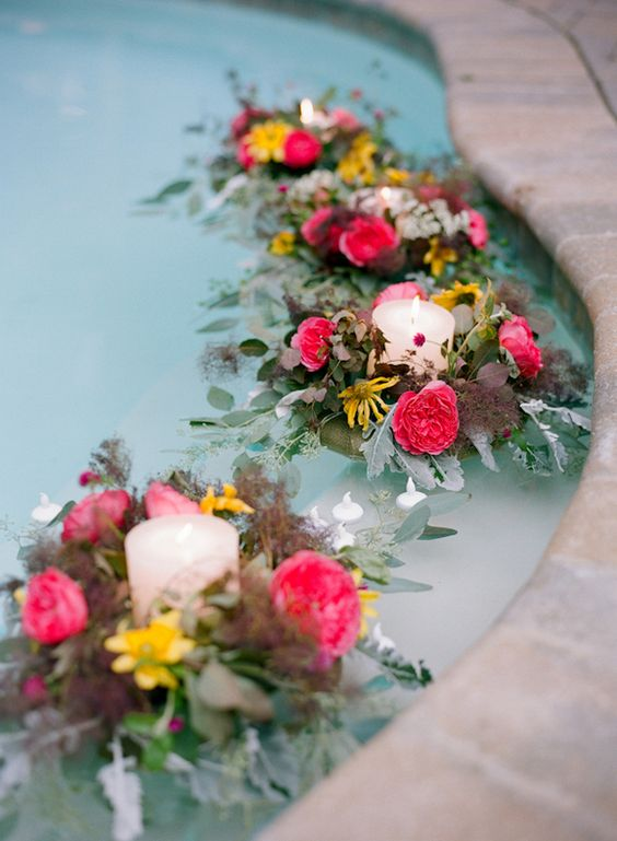 a pool with bold blooms and pale leaves plus candles floating here is a very chic and beautiful idea