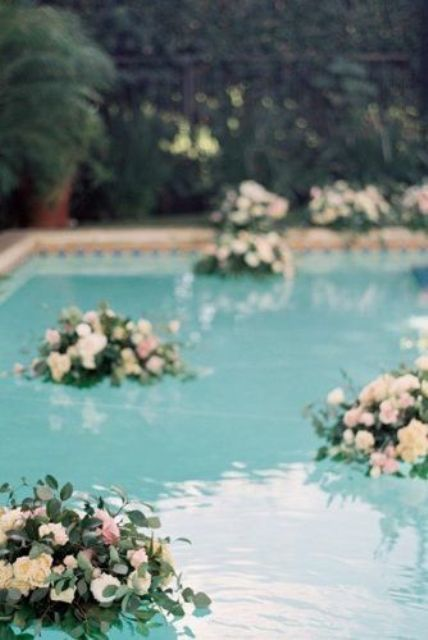 a pool with floating neutral and blush blooms and greenery is a very chic and beautiful idea for a refined wedding