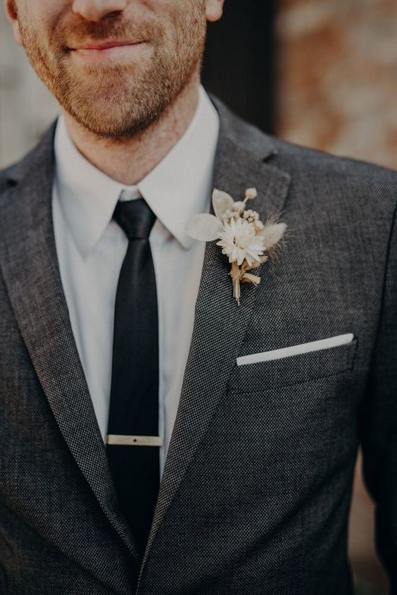 a pretty and small white wedding boutonniere with dired leaves, a bloom and some spikes is amazing for a modern fall wedding