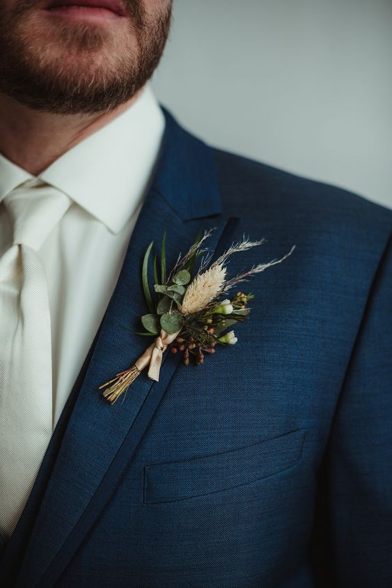a pretty fall wedding boutonniere with greenery, spikes, berries and some tan ribbon is a lovely idea for a neutral wedding