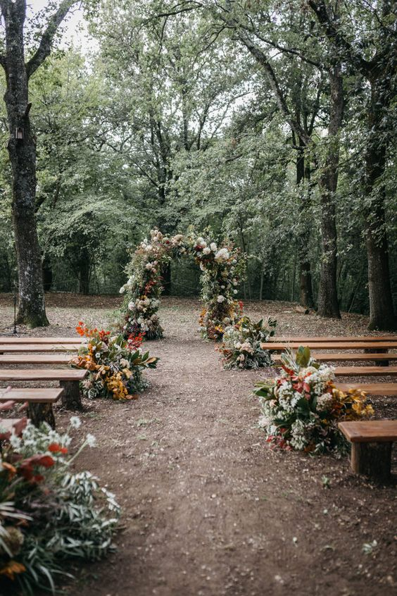 a pretty fall woodland wedding aisle with greenery, bright and white blooms and bold fall foliage is a creative idea