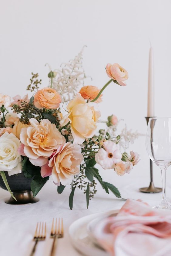 a pretty peachy and creamy plus blush floral wedding centerpiece with greenery and white candles in vintage candleholders