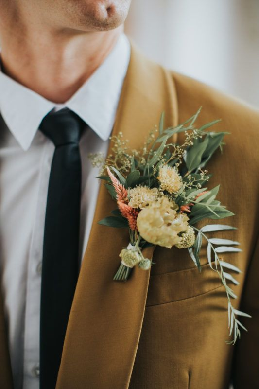 a pretty warm colored wedding boutonniere with orange and yellow blooms and grasses and greenery for a fall boho wedding
