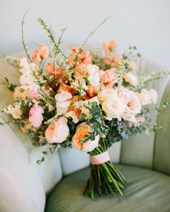 a pretty wedding bouquet with blush, orange and peachy flowers, greenery and blooming branches is very chic