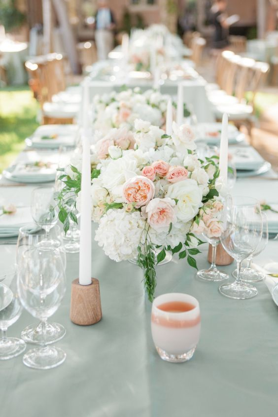 a pretty wedding tablescape with peachy, blush and white blooms, peachy candleholders and white candles for summer
