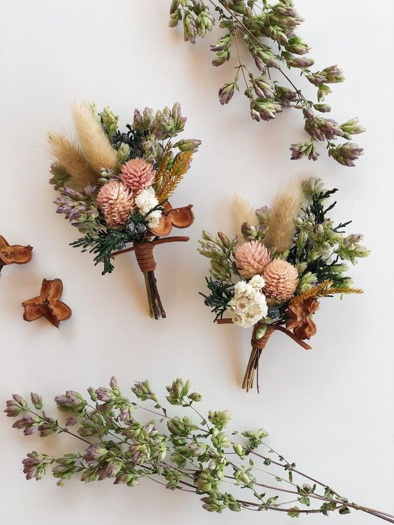 a refined dried floral boutonniere with neutral and pink blooms, spikes, greenery and leather straps is a super cool idea