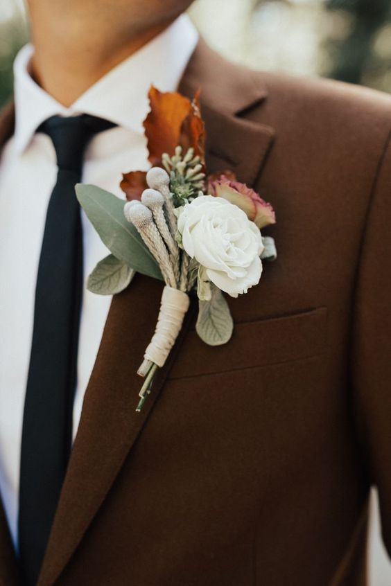 a refined fall wedding boutonniere with a pink and white bloom, greenery and rust leaves plus a bold fall leaf