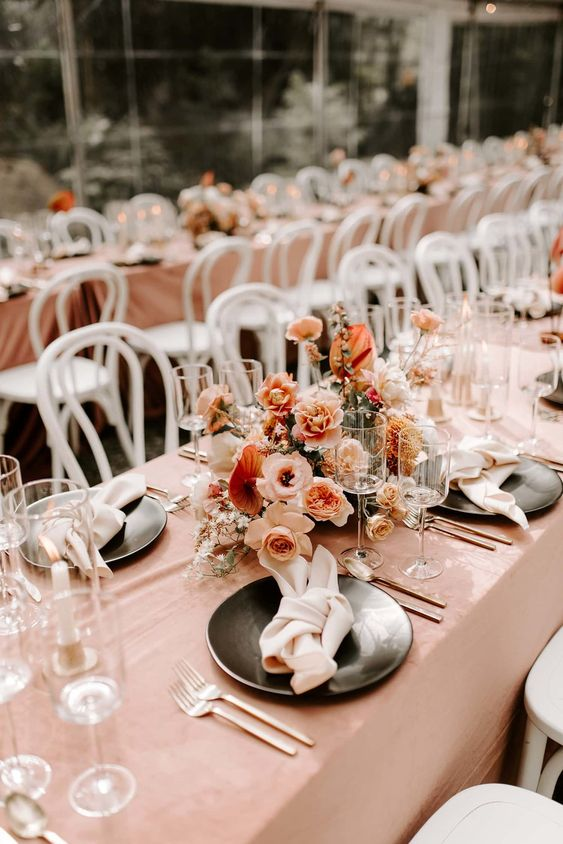 a refined peachy and cream wedding tablescape with a blush tablecloth, peahcy, blush and rust blooms and black plates and chic cutlery