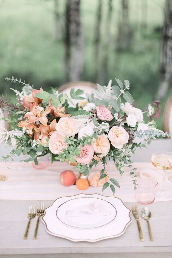a refined peachy wedding tablescape with peachy, pink and rust blooms and greenery, a peachy table runner and glasses plus gold cutlery
