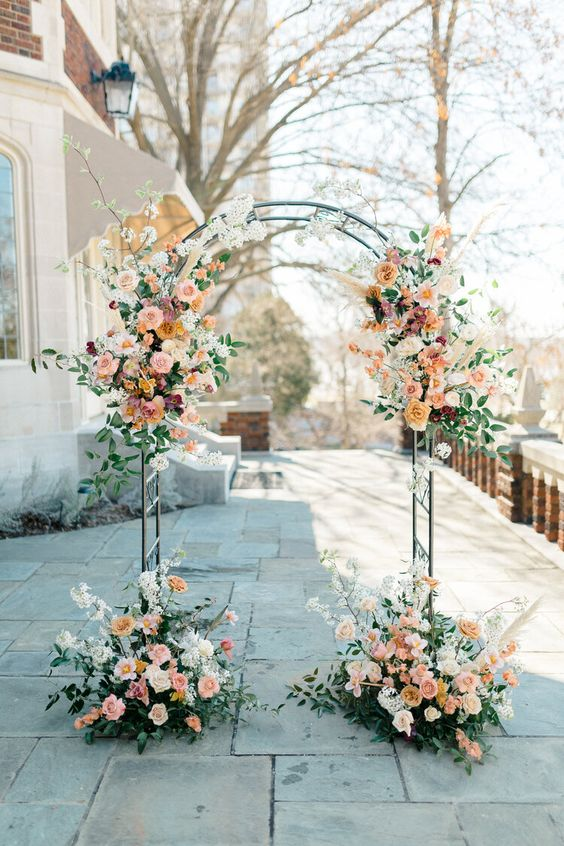 a refined wedding arch with blush, orange, peachy and mauve blooms, greenery and white blooming branches is chic