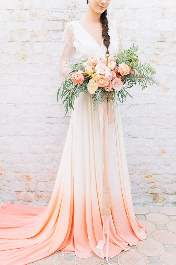 a refined wedding dress with a lace bodice and sleeves and a white to peachy pink skirt with a train looks beautiful