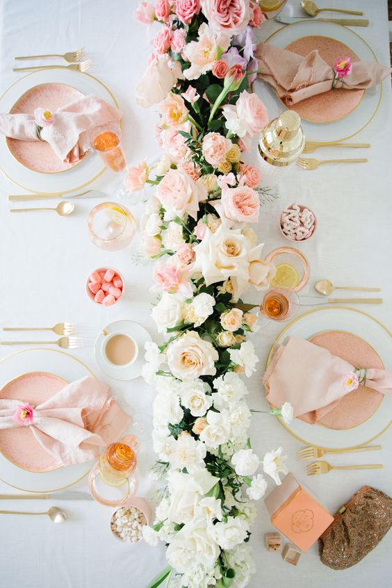 a refined wedding table setting with peachy plates and napkins, white, blush and peachy blooms and greenery plus candies