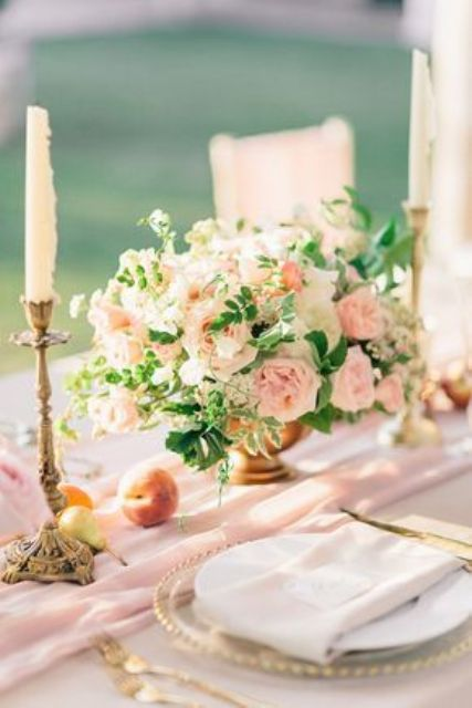 a refined wedding tablescape with a pink runner, peachy and blush blooms and greenery, candles, fresh fruits on the table