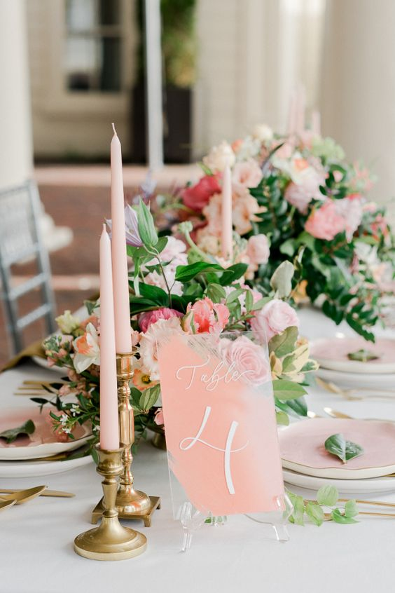 a refined wedding tablescape with peachy plates, candles and a table number and beautiful peachy and coral blooms with greenery