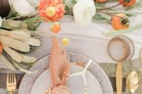 a romantic pastel tablescape with bright and neutral blooms and fruits on the table plus gilded touches